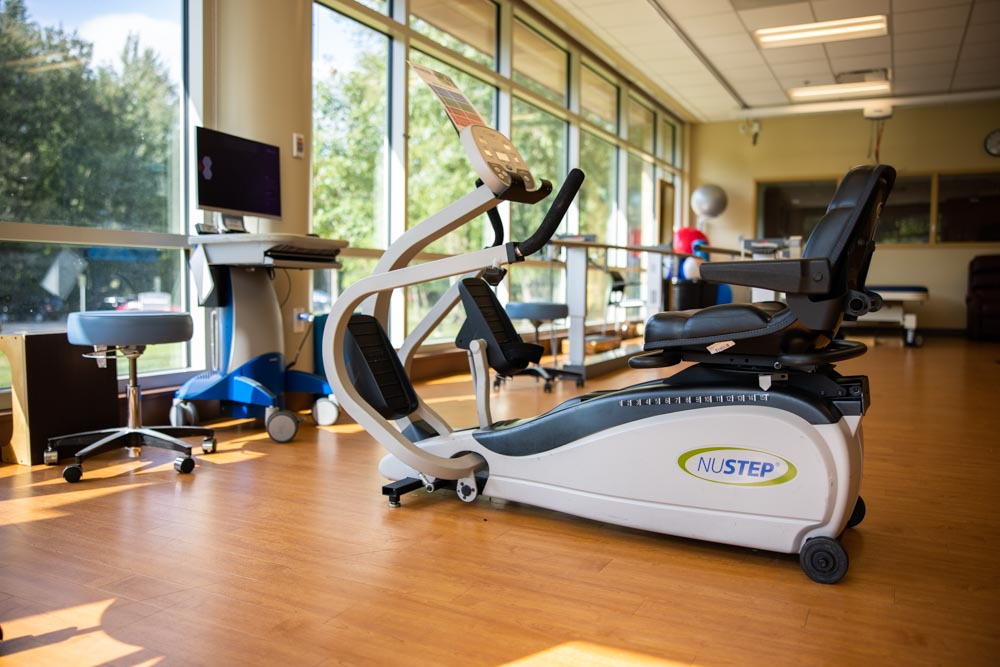 Rehab gym with wooden floor and wall of windows showing a NuStep rehab mcahine with a seat, pedals and hand levers