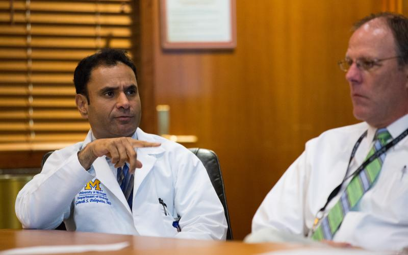 One doctor addresses colleagues seated at a conference table