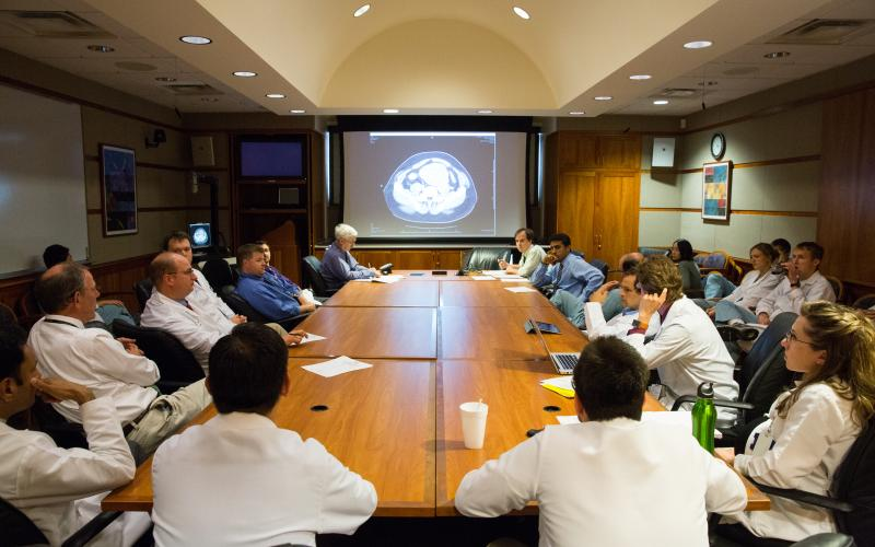 Doctors seated around a conference table with a radiology scan projected at the front of the room