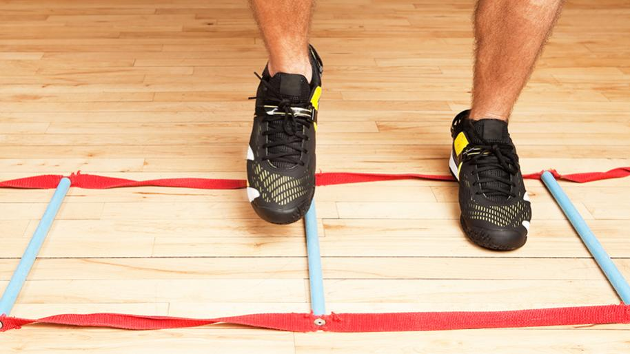 Lower legs of male wearing black athletic shoes hopping on a wood gym floor