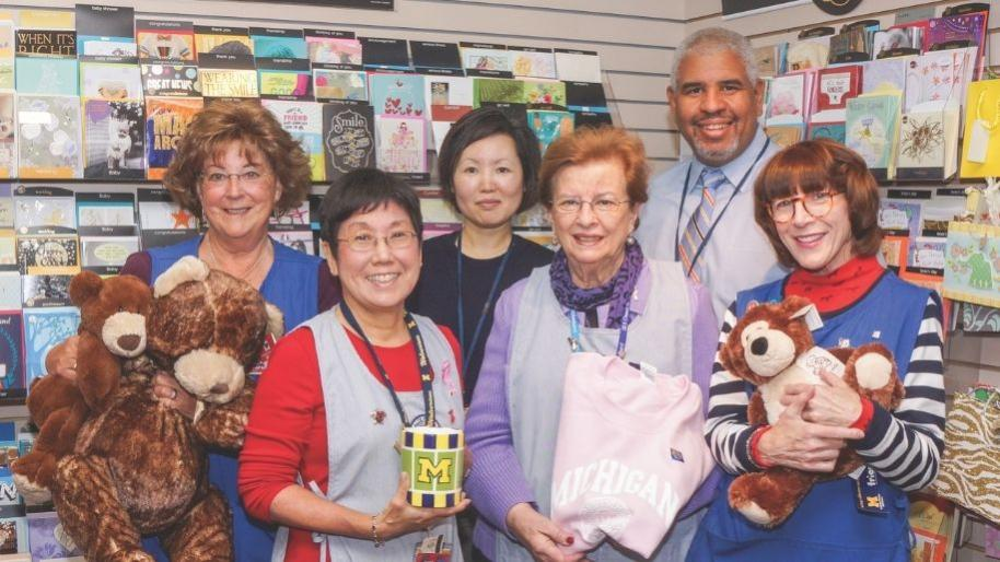 Diverse group of people smiling and standing in front of gift card display and holding gift items
