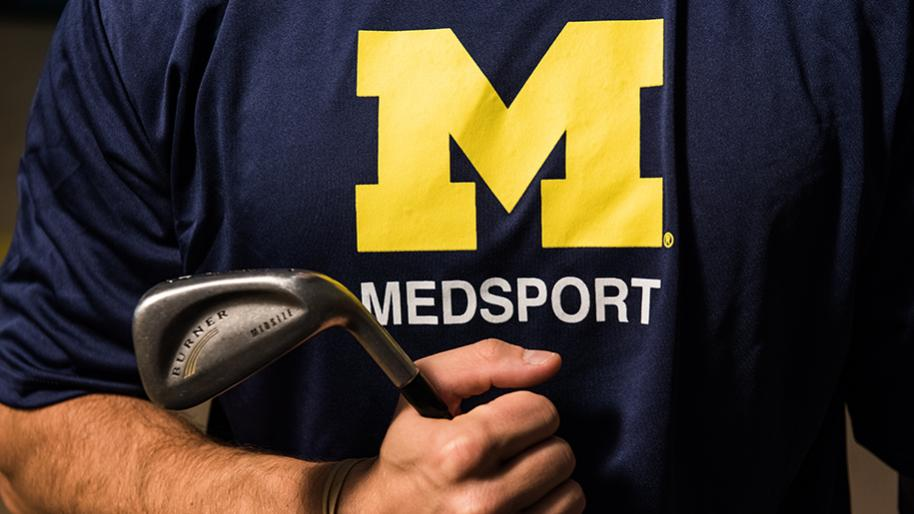 Torso of male holding a golf club and wearing navy blue t-shirt with maize block M and MedSport