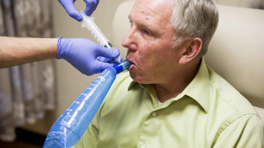 Man breathing into tube for hydrogen breath test