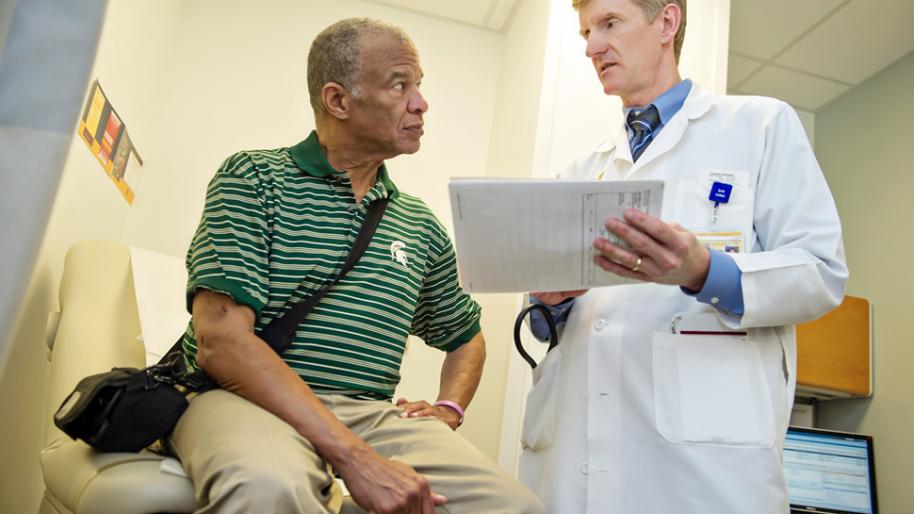 Seated LVAD patient Jerome Wilson and Dr. Todd Koelling discuss heart failure treatment