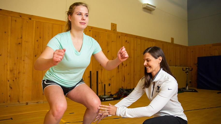 Femail trainer in white half-zip sweatshirt adjusting knee angle of young woman with knees bent and ready to jump