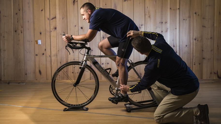 Male kneeling on floor taking a measurement of a male seated on a bike stabilized in a stand