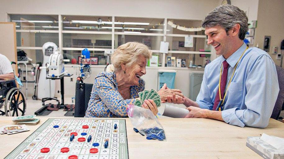 Dr. Edward Claflin with a patient playing a game and smiling