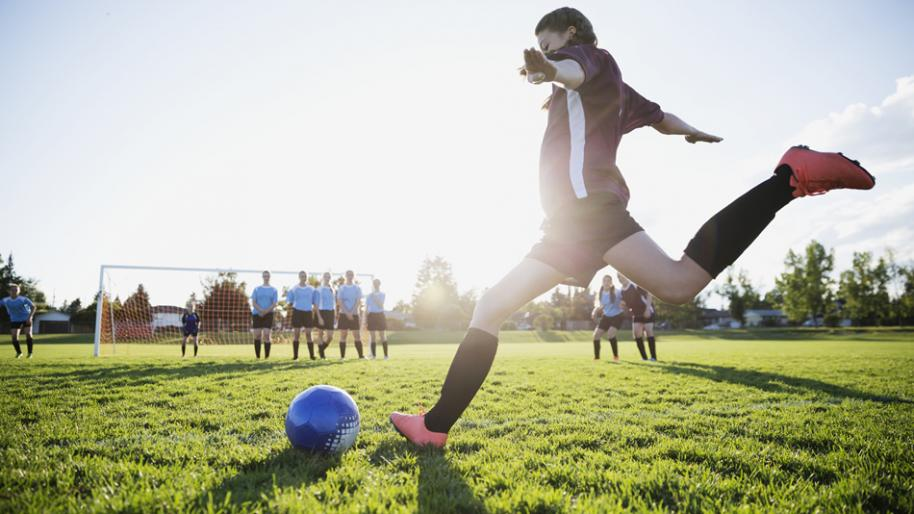 Female soccer player ready to kick a blue ball