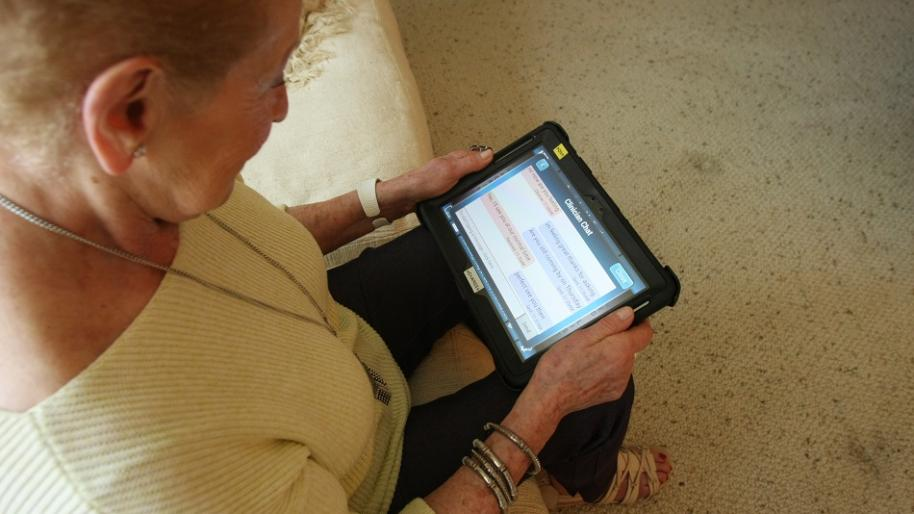 "Side view of older woman seated and looking at digital tablet with words ""Clinician Chat"" visible"