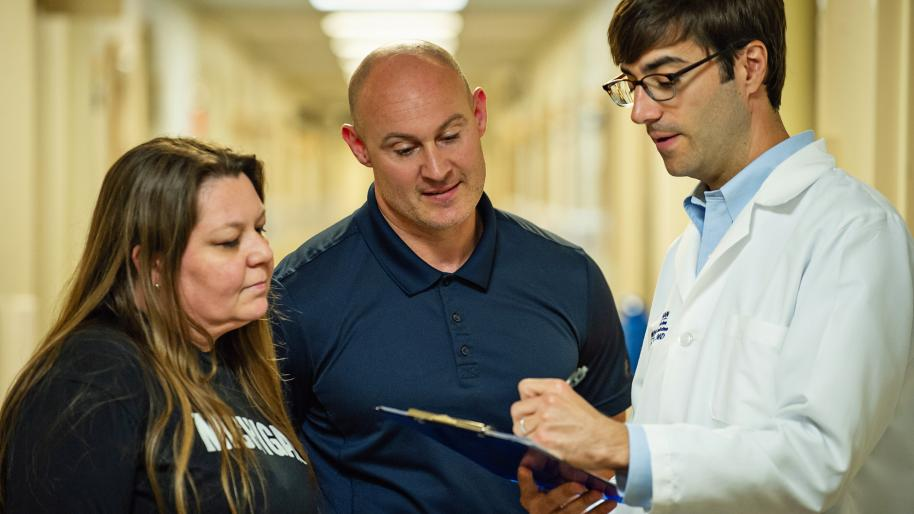 Dr. Jakob McSparron wearing white coat and writing on clipboard talking to bald man in blue polo shirt and woman with long brown hair wearing blue t-shirt with word Michigan in white letters