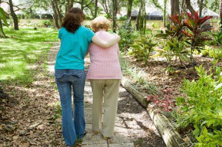 Caregiver helps woman walk