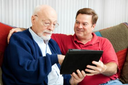 Son teaching older dad to use tablet