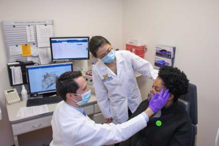 Two doctors examining patient's facial movements