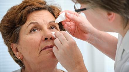Doctor administering eye drops to middle age woman