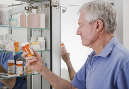 Man taking pills from medicine cabinet