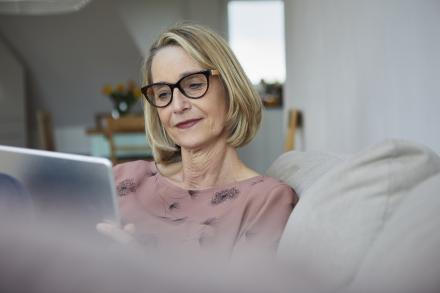Older woman sitting on couch using a tablet