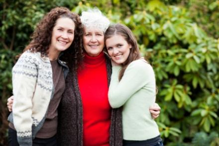 A older woman hugs her daughter and granddaughter