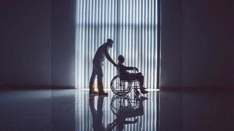 COVID-19 patient being pushed in a wheelchair by a man in PPE