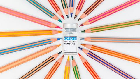 Colored pencils surrounding a vial of COVID-19 vaccine