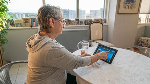 Woman looking at tablet with medication near