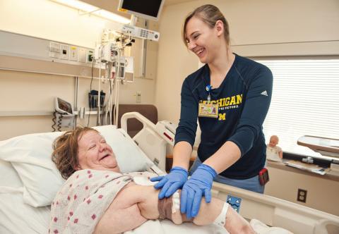 U-M nurse assisting patient