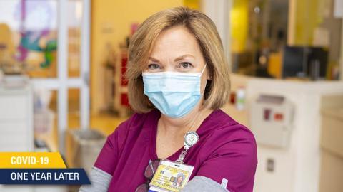 White nurse with blond hair in fuschia scrubs wearing mask