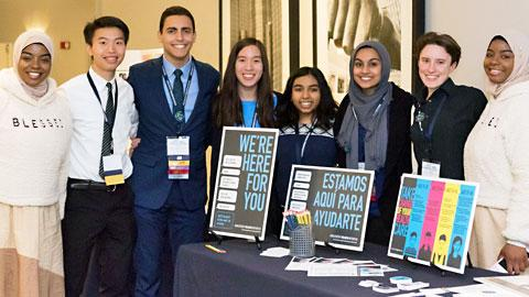 "Group of Black, Brown, Asian and Caucasian male and female teenagers standing behind a table with a signs in English and Spanish that read ""We're here for you"""