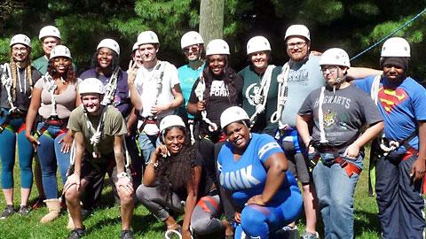 Group of 15 Black and  White young people wearing white helmets and harnesses standing and smiling at the camera in front of trees