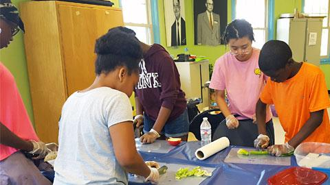 Black and Brown teenagers chopping celery on two sides of a table covered with a blue plastic tablecloth