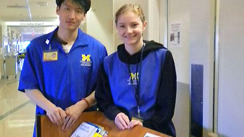 Young Asian man and young woman with blonde hair, both standing and smiling, wearing blue shirts with Michigan block M logo in maize