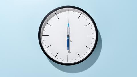 Round white clock on pale blue background with hashes instead of numbers and vaccine shot instead of clock hands pointing straight up