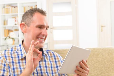 deaf man signing with tablet