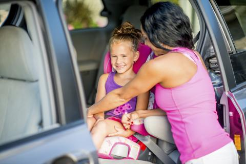 Mom buckling in child in car seat
