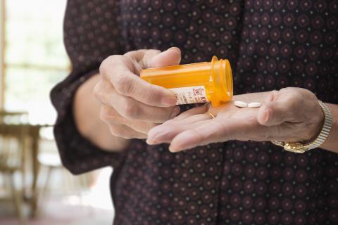 woman holding prescription pill bottle
