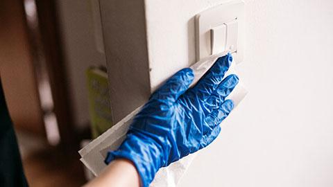 Gloved hand wiping a light switch with a disinfecting wipe