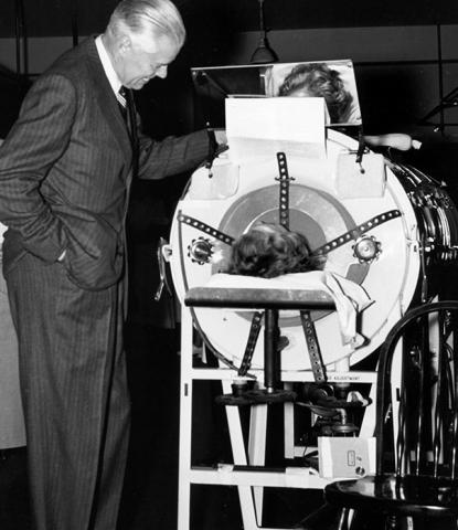 U-M president Harlan Hatcher with an iron lung patient