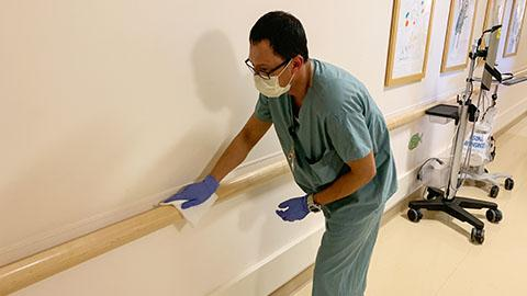 Man in scrubs, surgical mask, and gloves wiping down the rainling the the hospital hallway