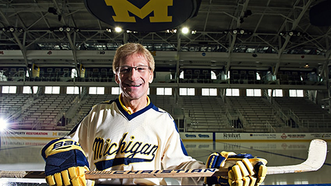 Ray Dries, former University of Michigan hockey player, at Yost Ice arena wearing a Michigan jersey & holding a hockey stick
