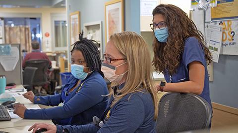 Image of 3 nurses at a nursing station looking at at a monitor