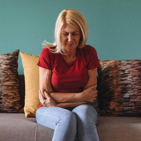 Woman sitting on a sofa with her arms over her tummy.