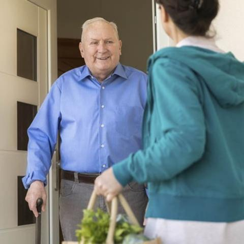 Older man opening the door to a younger person delivering his groceries.