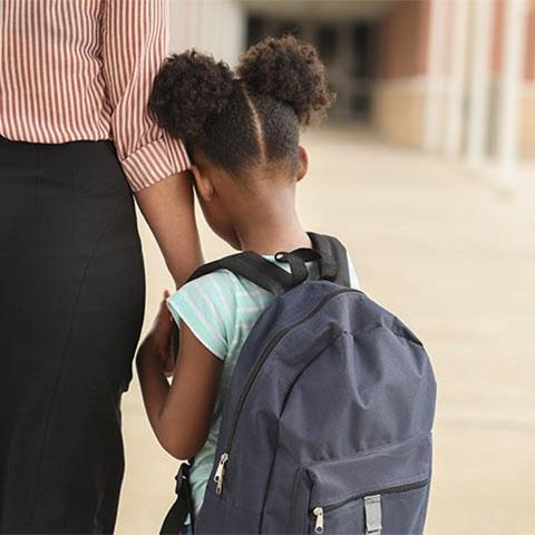 little girl wearing a backpack leaning her head against her mom's arm