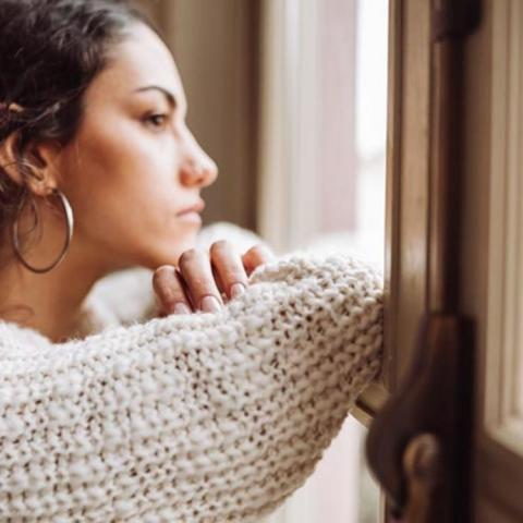 Woman wistfully looking out a window