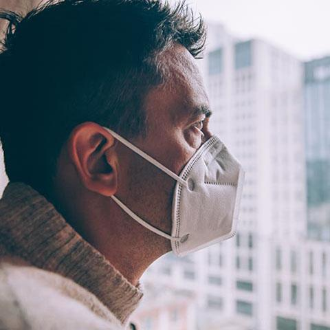 Man in a breathing mask look out a window at a city scape