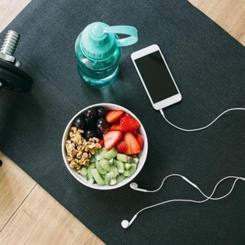 Fruit and granola in a bowl, blue water bottle, iphone with headphones on a black mat