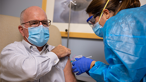 Female health care worker wearing PPE giving shot to bald middle-aged male wearing glasses and a mask