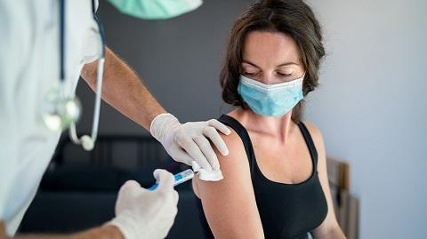 White woman wearing black tank top and a mask getting a shot