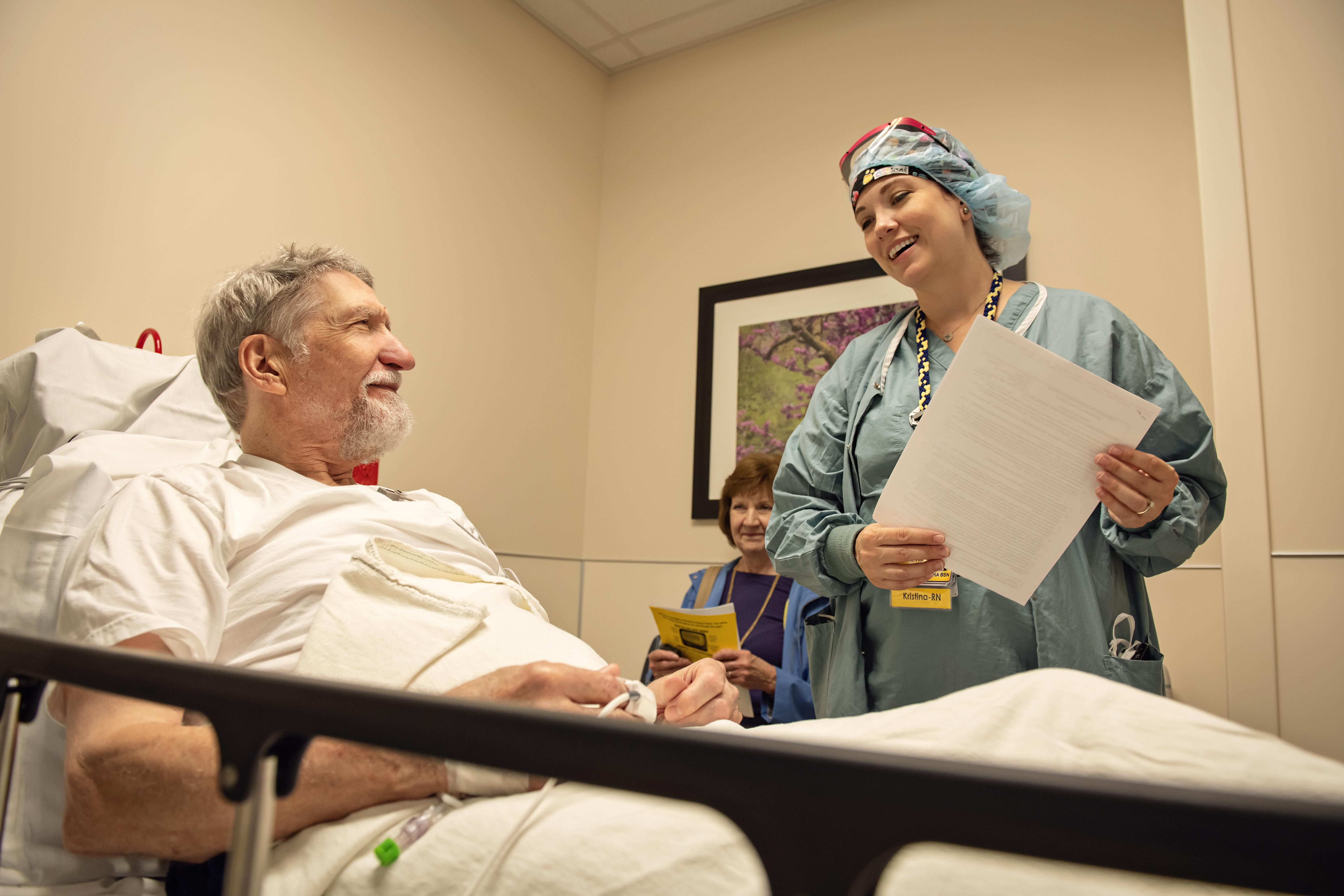 Man laying on hospital bed talking to nurse