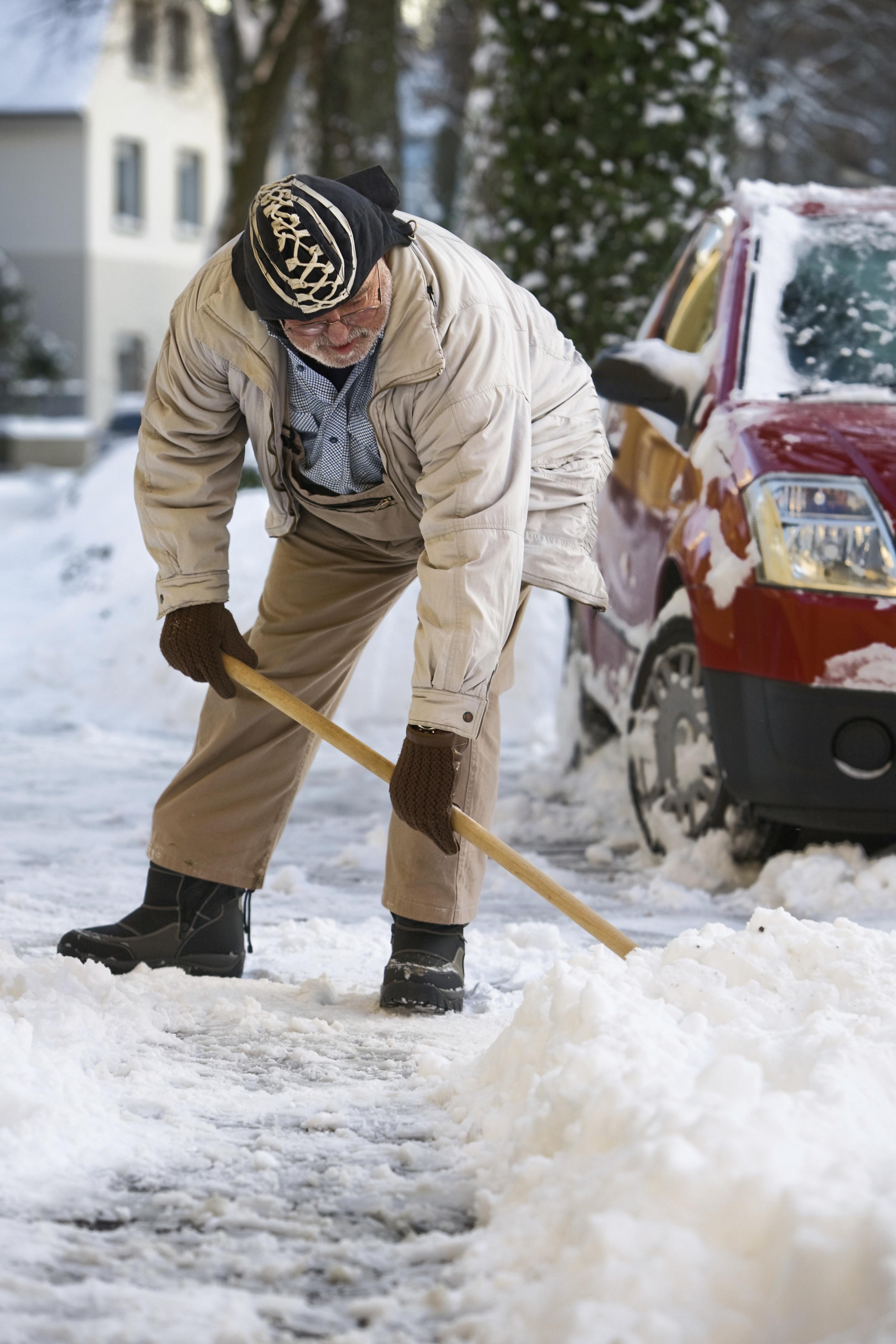 Older man shovelling snow