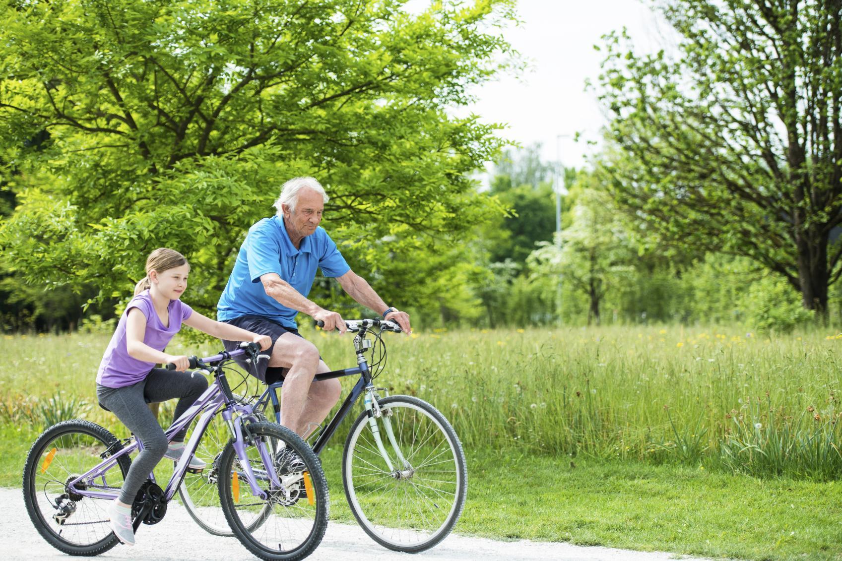 Young girl biking with grandpa